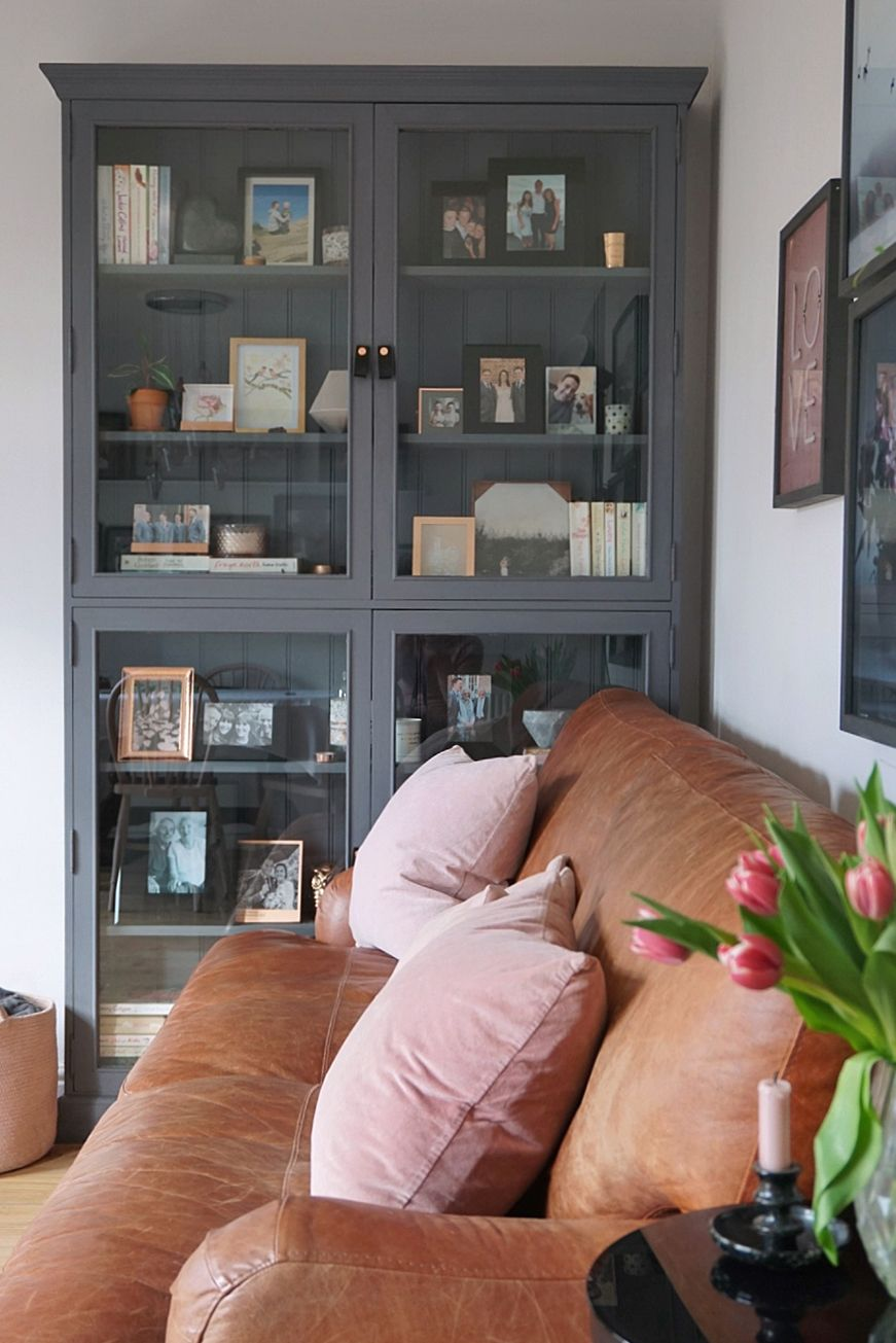 vintage bookcase tan leather sofa pink cushions